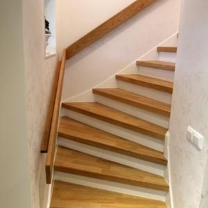 Stängd trappa i Ek 3-stav med vitmålade sättsteg och handledare.